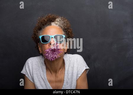 Studioportrait senior Frau mit Blume im Mund - Stockfoto