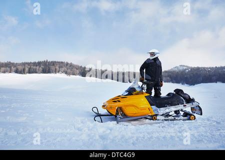 Mitte erwachsener Mann mit Motorschlitten, Togwotee Pass, Wyoming, USA - Stockfoto