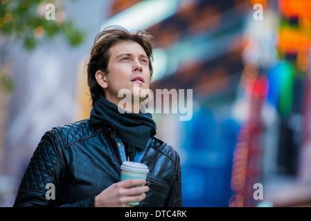 Junge männliche Touristen mit Kaffee zum mitnehmen, New York City, USA - Stockfoto