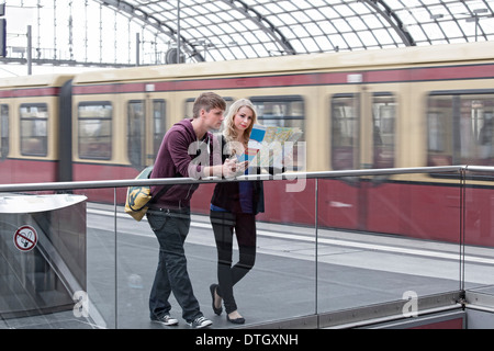 Junges Paar auf der Plattform mit Blick auf eine Karte, Berlin, Deutschland - Stockfoto