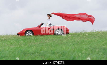 Frau in einem Cabrio Vermietung ein rotes Tuch flattern im Wind, Deutschland - Stockfoto