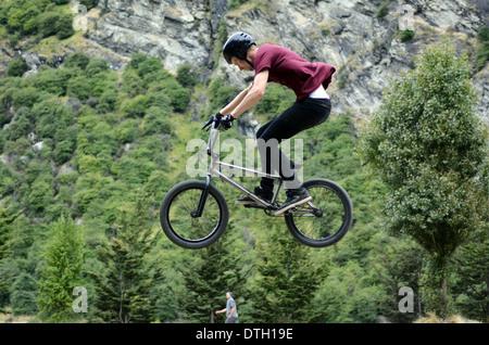 Junger Mann führt einen Trick mit seinem BMX-Rad in Queenstown, Neuseeland - Stockfoto