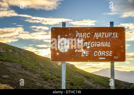 Parc Natural De Corse Wegweiser gespickt mit Jägers Einschusslöcher gegen eine aufgehende Sonne - Stockfoto