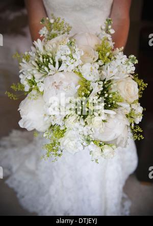eine Braut hält ein Brautstrauß Pfingstrosen und weißen Blumen Rosen hautnah - Stockfoto