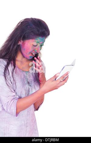 Frau feiern Holi und Benutzung eines Mobiltelefons - Stockfoto