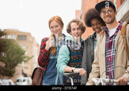 Freunde, die zusammen auf Stadtstraße lächelnd - Stockfoto