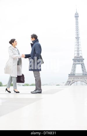 Geschäftsleute, die Hände schütteln in der Nähe von Eiffelturm, Paris, Frankreich - Stockfoto