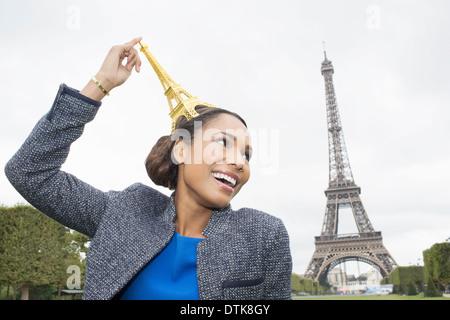 Frau posiert mit Souvenir vor Eiffelturm, Paris, Frankreich - Stockfoto