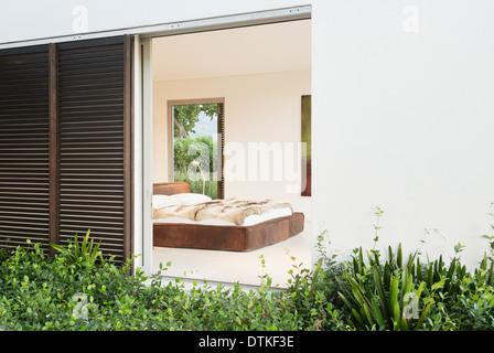 Hölzerne Blendenverschlüsse und Schiebetür zum modernen Schlafzimmer - Stockfoto