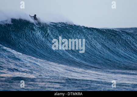Surfer paddeln über eine große Welle im Ozean - Stockfoto