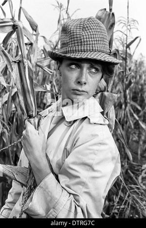 60er Jahre Mode Regenmantel mit Hut posiert in einem Maisfeld - Stockfoto