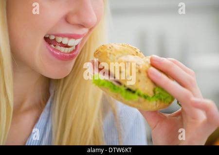 Closeup auf junge Frau Sandwich zu essen - Stockfoto