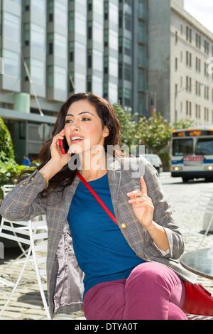 Gemischte Rassen Frau auf Handy in städtischen Straßencafé - Stockfoto
