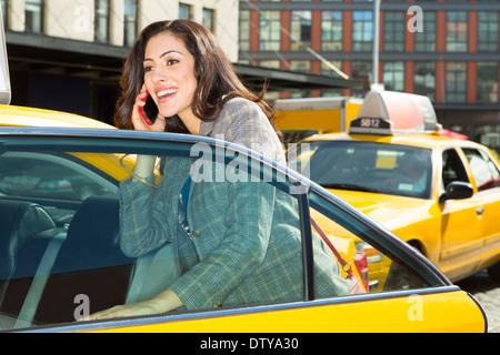 Gemischte Rassen Frau bekommen in taxi - Stockfoto