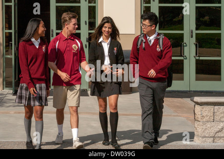 Kaukasischen, asiatisch-amerikanische und Afroamerikaner uniformierten Studenten zu Fuß, auf dem Campus der katholischen - Stockfoto