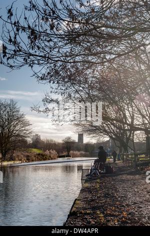 Fischer und Wanderer am Kanal in Middlewich, Cheshire, mit Pfarrkirche im Hintergrund und Winter Bäume im Vordergrund. - Stockfoto
