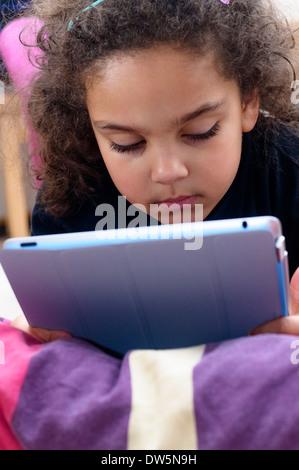 Young Little Girl nutzt Ipad während liegend auf dem Sofa - Stockfoto