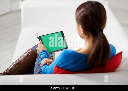 Porträt der schönen Asiatin mit Tablet-pc mit Greenscreen, sitzt zu Hause auf sofa - Stockfoto