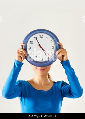 Porträt von asiatischen Geschäftsfrau versteckt sich hinter blauen Uhr und mit Blick auf die Kamera zu Lächeln - Stockfoto