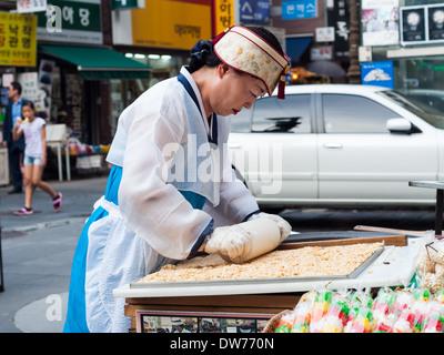 Eine Frau bereitet Reis Kuchen Snacks auf einem Marktplatz in Insadong, Seoul. - Stockfoto