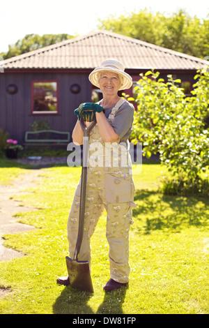 In voller Länge Portrait aktive senior Frau Hut mit Gartengeräten lächelnd im Freien. Ältere Frau mit Schaufel. - Stockfoto