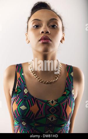 Porträt der jungen Frau, Blick in die Kamera mit einer Haltung. Schöne weibliche Model posiert auf grauem Hintergrund - Stockfoto