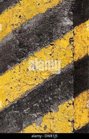 Schwarz-gelb gestreiften Vorsicht Muster auf alte Betonmauer - Stockfoto