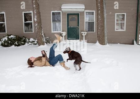 Mitte Erwachsene Frau im Schnee draußen spielen mit Hund Haus liegen - Stockfoto