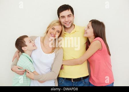 Porträt von liebevollen vierköpfige Familie posiert auf weißem Hintergrund - Stockfoto