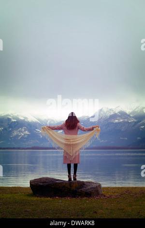 an einem See steht eine Frau in einem rosa Mantel mit einem weißen Schal - Stockfoto