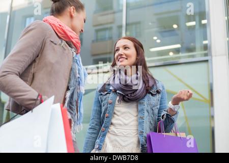 Niedrigen Winkel Ansicht von Freundinnen mit Einkaufstüten sahen einander gegen Shop - Stockfoto
