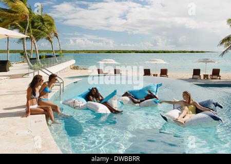 Gruppe junger Erwachsener Entspannung in Schwimmbad, Providenciales, Turks-und Caicosinseln, Caribbean - Stockfoto