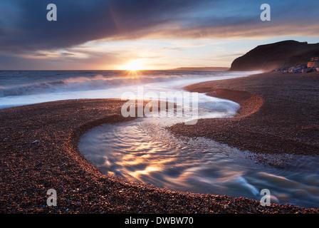Fluß Winniford fließt in das Meer am Strand der einladendsten mit den Klippen von Golden Cap in der Ferne. Jurassic - Stockfoto