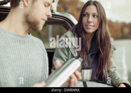 Junge Frau Blick auf Menschen, die Kaffee für sie gießt - Stockfoto