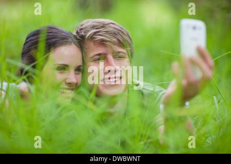 Junges Paar selbst fotografieren auf Rasen - Stockfoto