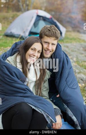 Porträt des glücklichen Paares in Decke gegen Zelt im Wald gehüllt - Stockfoto