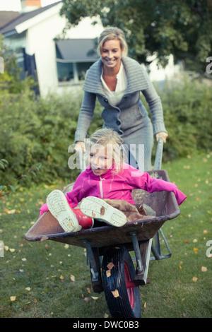 Spielerische Mutter schob Tochter auf Schubkarre am Hof - Stockfoto