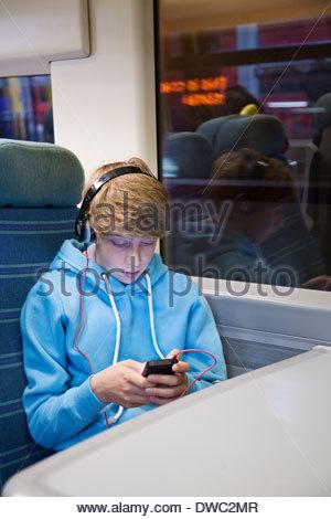 Teenager im Kopfhörer und mit Smartphone auf Zug - Stockfoto