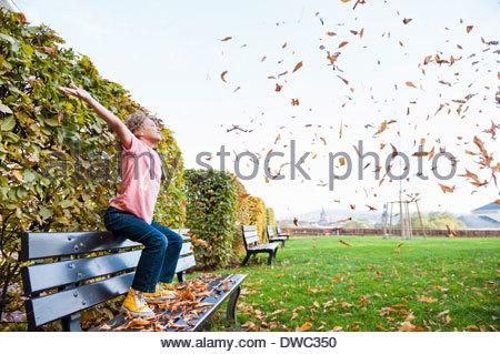 Junge sitzt Streuung Blätter in Luft - Stockfoto