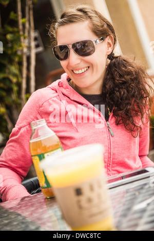 Junge Frau mit Fruchtsaft in Straßencafé - Stockfoto