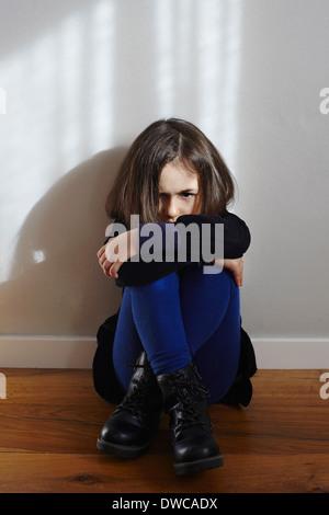 Porträt von hartnäckigen junges Mädchen am Boden knien umarmt - Stockfoto