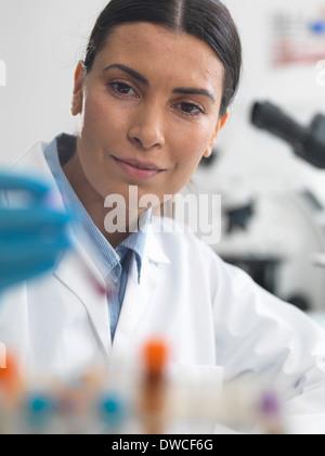 Wissenschaftlerin zu eine Probe unter dem Mikroskop ansehen Stockfoto
