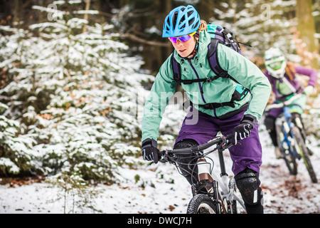 Zwei weibliche Mountainbiker fahren durch Wald im Schnee - Stockfoto