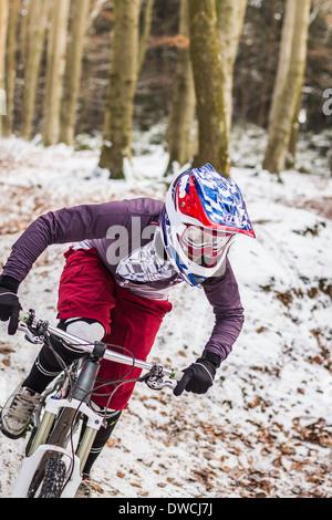 Junge weibliche Mountainbiker bergab durch Wald - Stockfoto
