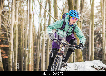 Weibliche Mountainbiker fahren durch Wald - Stockfoto