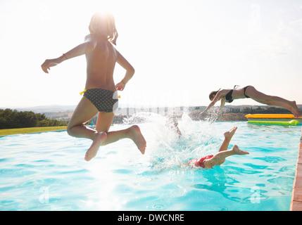 Drei Personen ins Schwimmbad springen - Stockfoto