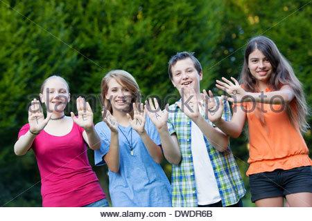 Drei Mädchen und ein Junge, die zusammen die Wort Teenager auf ihre Handflächen zeigen - Stockfoto