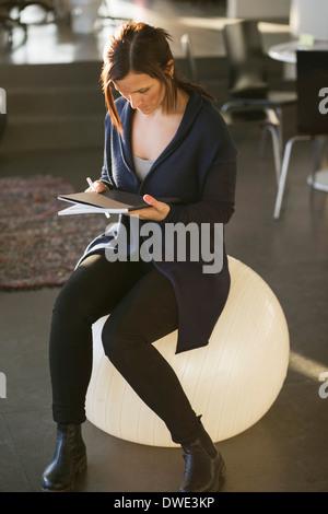 Geschäftsfrau, die Zeitschrift zu lesen, während auf Fitness-Ball im Büro sitzen - Stockfoto