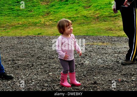 Kleines blondes Mädchen in rosa Hemd und Wellington boots - Stockfoto