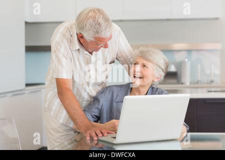 Gerne älteres Paar mit dem Laptop am Tisch - Stockfoto